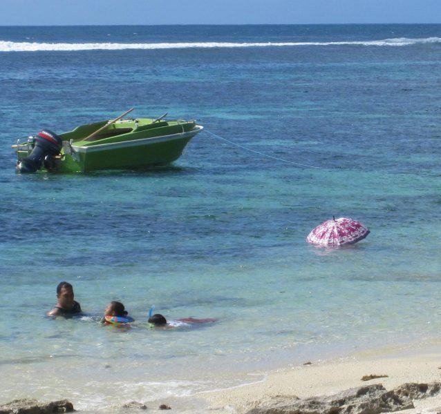 Person swimming under umbrella, Ha-atafu Beach, Tongatapu, Tonga
