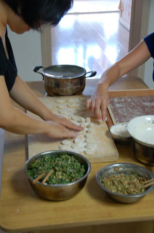 Flattening the dough portions.How to make Chinese Dumplings (Jiaozi)