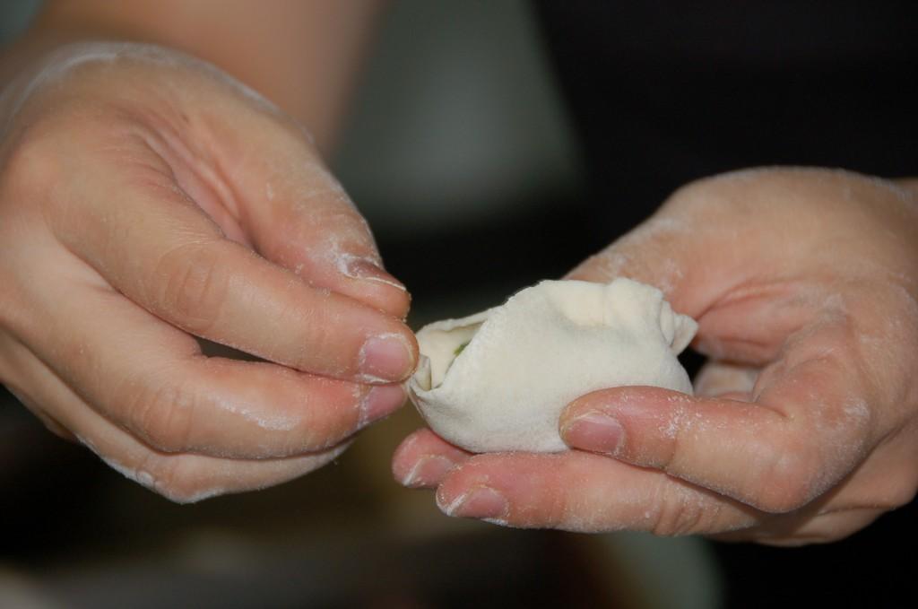 Pinching the dumpling skin closed.How to make Jiaozi