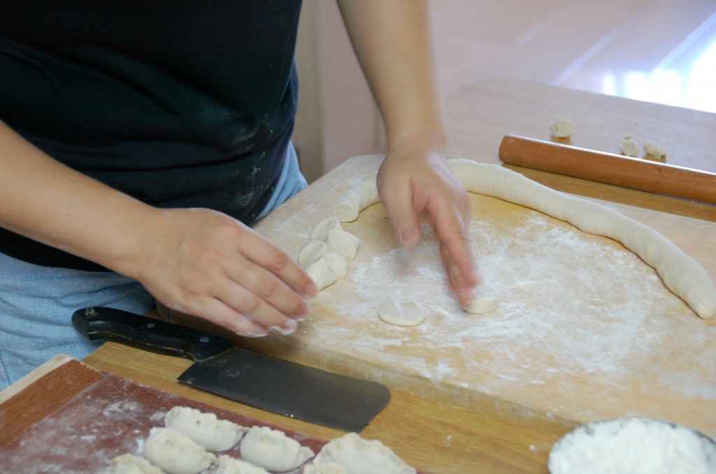 Laurette creating the dumpling skins (and you can also see the stuffed, uncooked dumplings to the left).