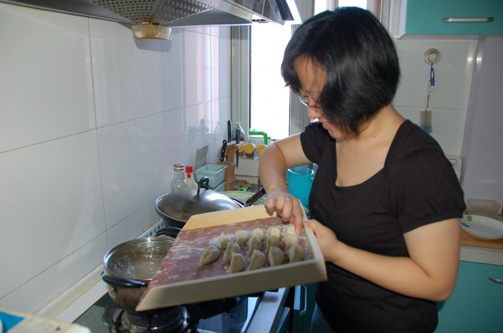 Laurette pushing the dumplings into boiling water.How to make Chinese Dumplings.Jiaozi