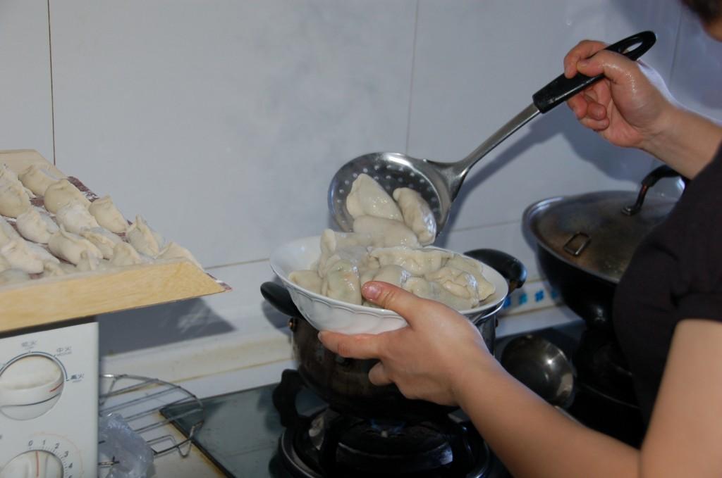 Scooping freshly boiled dumplings (Jiaozi) from boiling water