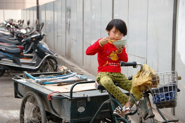 Little girl eating noodles.Xian China