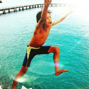 Boy diving for coins off ferry