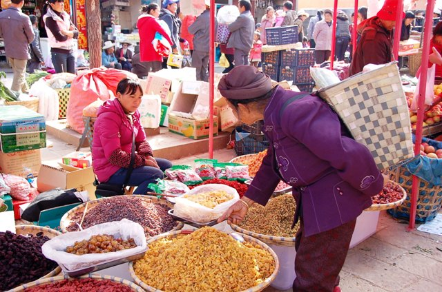 Shaxi Friday Market. The basket this woman is wearing is commonly seen here.