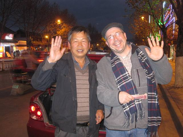 Our driver waving goodbye outside Lijiang Old Town (he wanted Sam in the picture, too!)