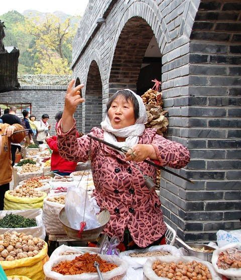 "Vendor weighing fruit and gesturing, ""20 Kwai!"" (RMB)"