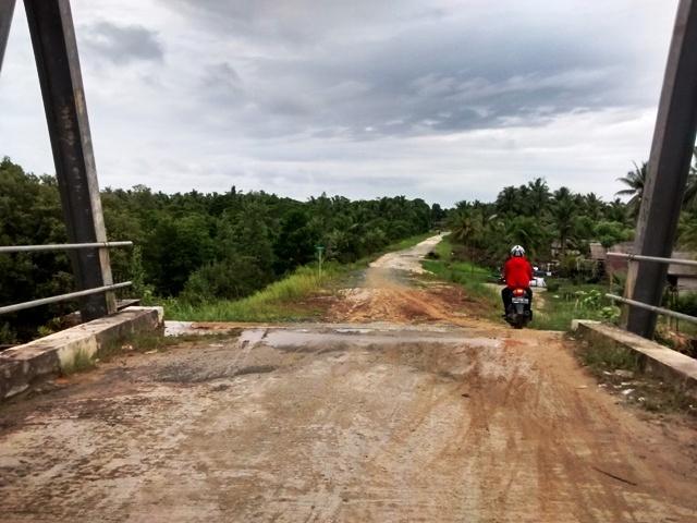 Bridge to dirt road leading to Penajam fields and beaches. Kalimantan, Indonesia