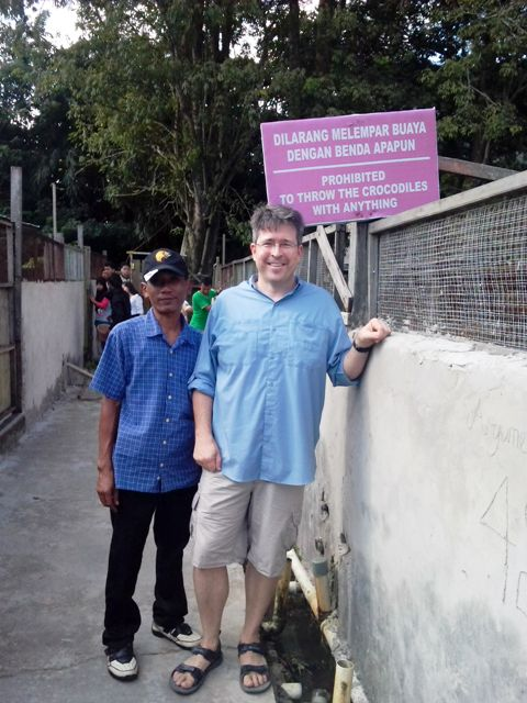 Sam and Pak Nurul (our driver) at Crocodile Farm. Love the sign!