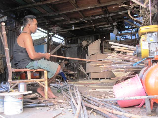 Local wicker factory behind wicker store. Men are stripping rattan and bamboo harvested from the forest.