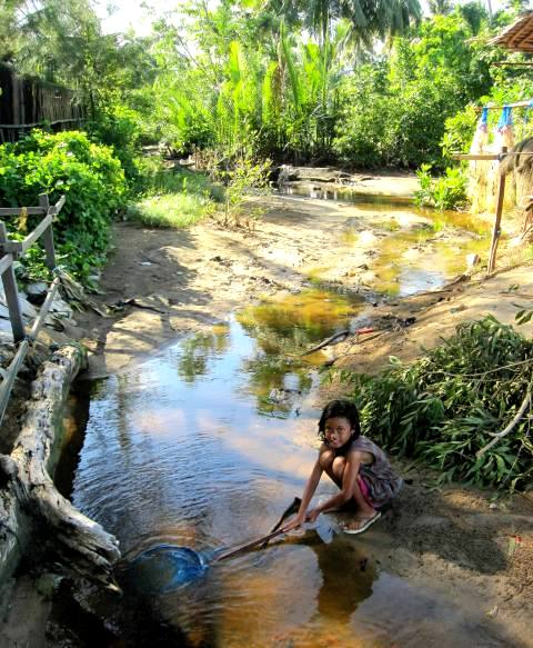 Girl fishing in creek.Manggar Beach