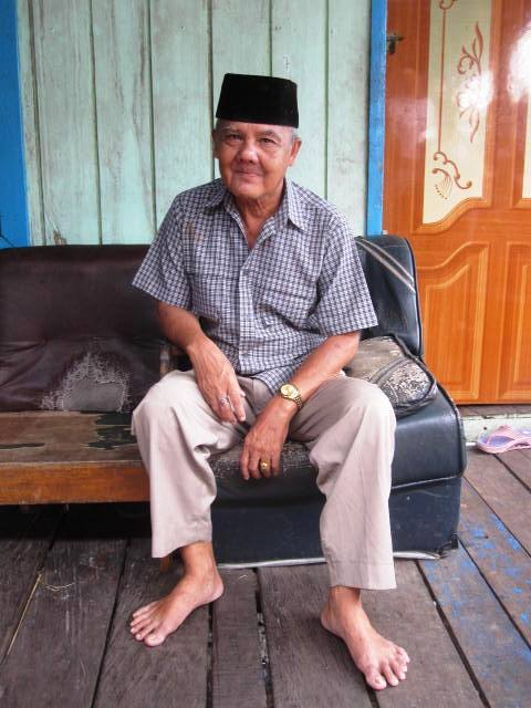 Man in Muslim cap, sitting outside home in Kampung Baru, Balikpapan.