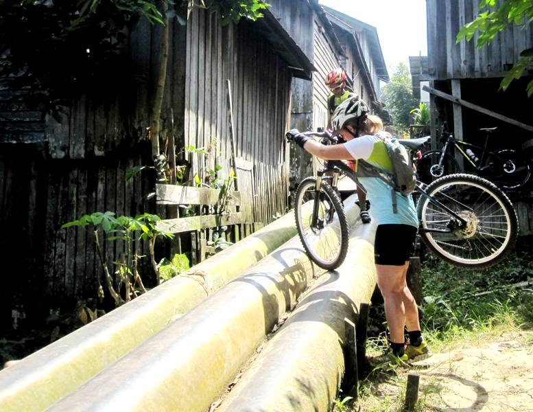 Anneke lifting bike over Pertamina water pipes.BIWA cycling group