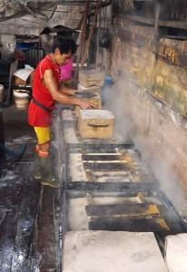 Adding concrete weights to press tofu molds.Indonesia tofu factory