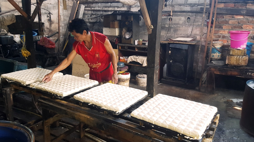Cutting freshly molded tofu. Balikpapan, Indonesia Tofu Factory