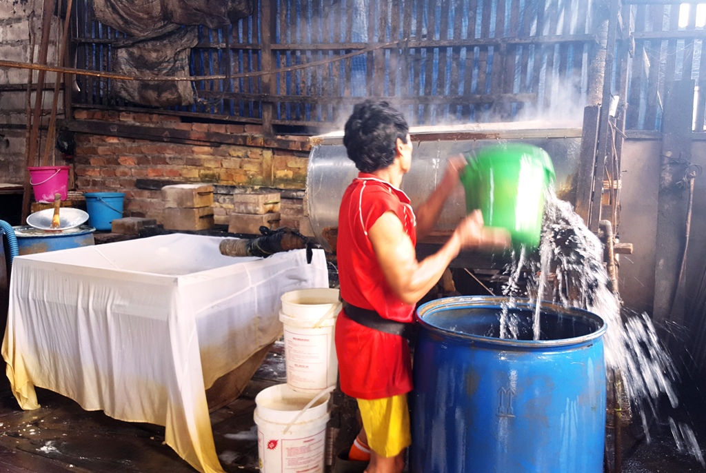 Pouring water into the soy paste prior to sieving. Balikpapan tofu factory, Indonesia