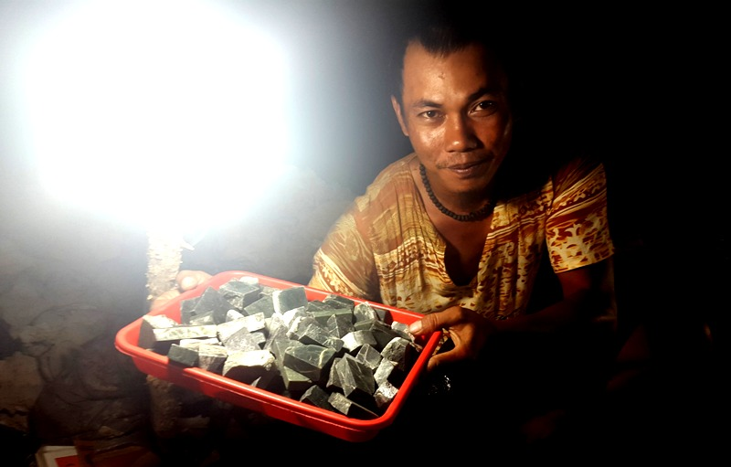 Merchant showing raw black stones.Balikpapan Indonesia