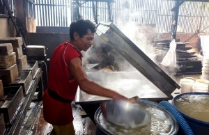 Mixing vinegar water with soy milk.Indonesia tofu factory