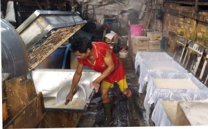 Scooping tofu curds into mold presses.Indonesia tofu factory