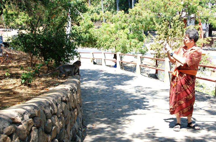 Wearing sash and sarong on walkway to Pura Pabean.Pemuteran Bali