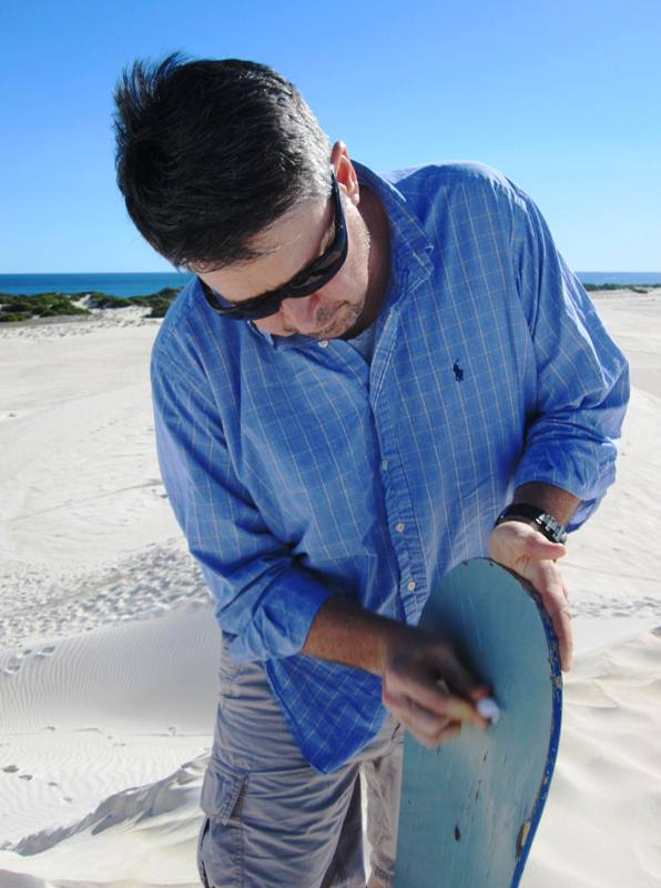 Waxing sand board at Lancelin Dunes.Western Australia