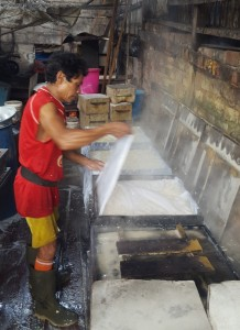 Wrapping fresh tofu curd with cheese cloth before pressing. Balikpapan tofu factory