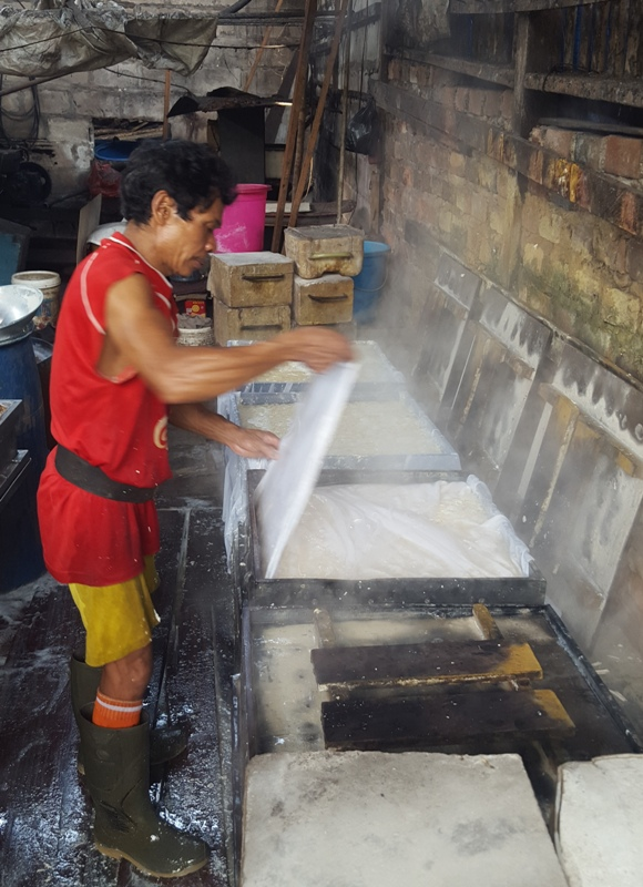 Wrapping fresh tofu curd with cheese cloth before pressing. Balikpapan tofu factory