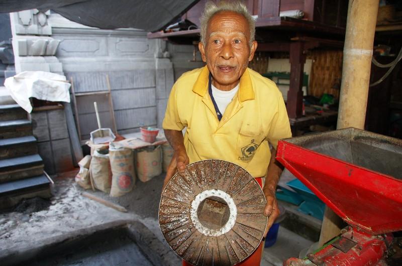 Pak Beni showing wheel used to de-skin coffee cherries.Munduk Bali