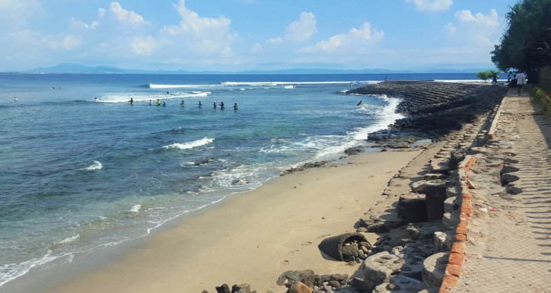 Beach Walk: Fishing near Senggigi Beach Point with surfers in the distance.Lombok, Nusa Tenggara, Indonesia