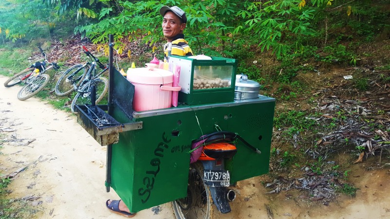 A motorcycle food kiosk selling steam and grilled bakso. Indonesian street food