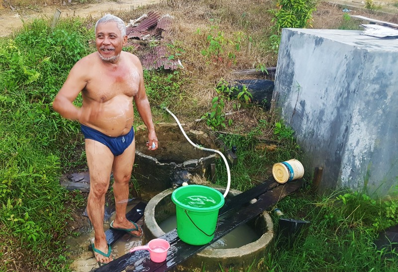 Man bathing at village spring. Balikpapan, Indonesia