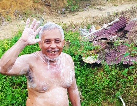 Sumarji taking a bath at the village spring near Balikpapan, Indonesia