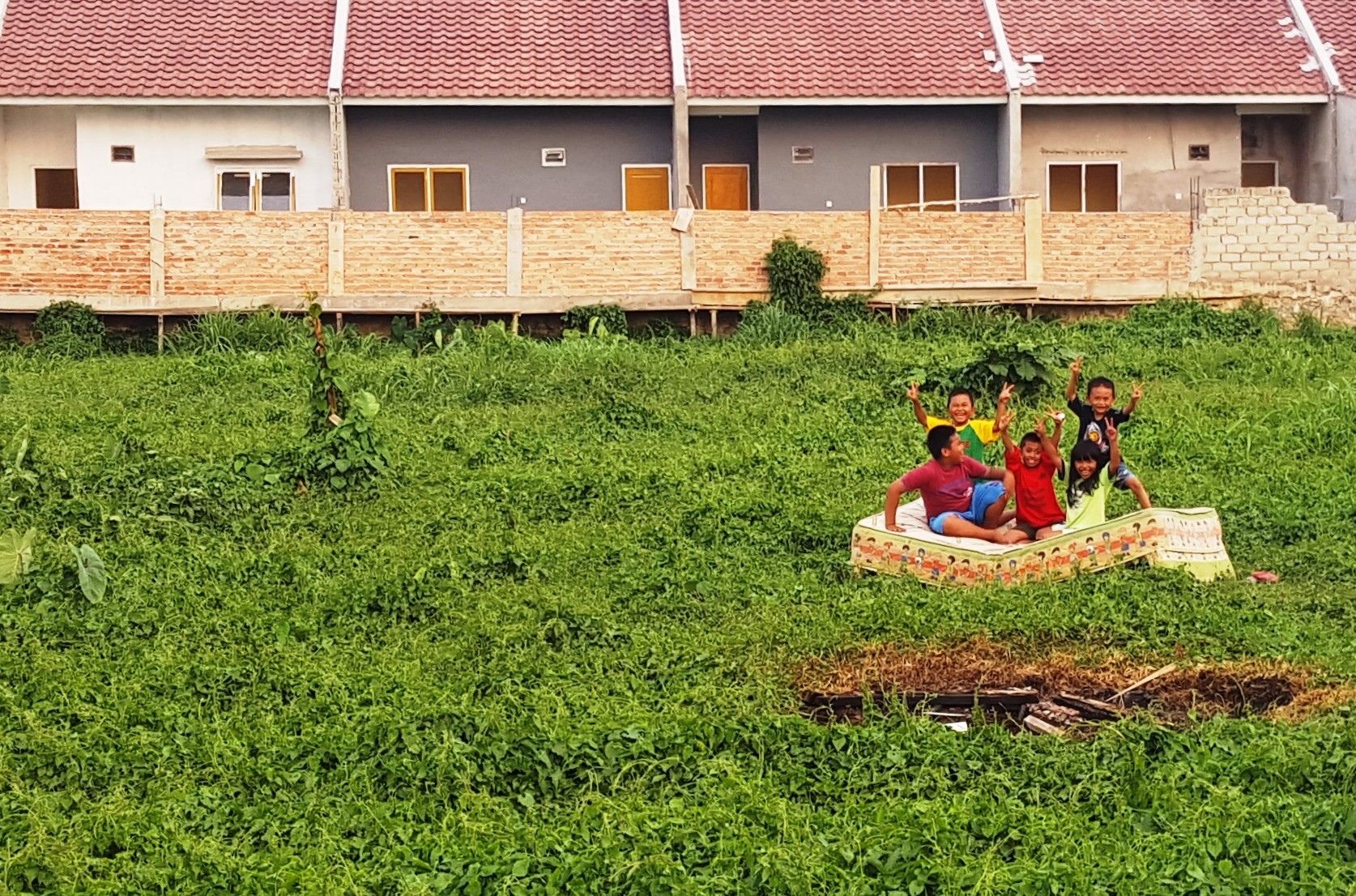 Children playing on a mattress outside Balikpapan housing complex, East Kalimantan, Indonesia