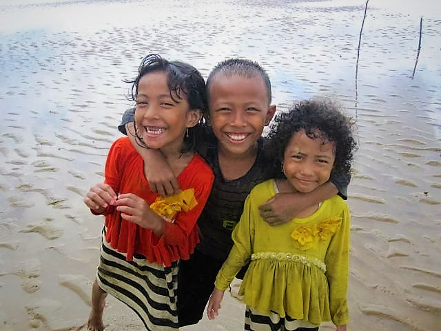 "Happy kids greeting me as I step into the low tide at Tanah Merah (""Red Earth"") Beach, Balikpapan, Indonesia."