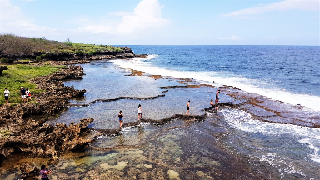Walking along the natural borders of Inarajan Pools, Guam